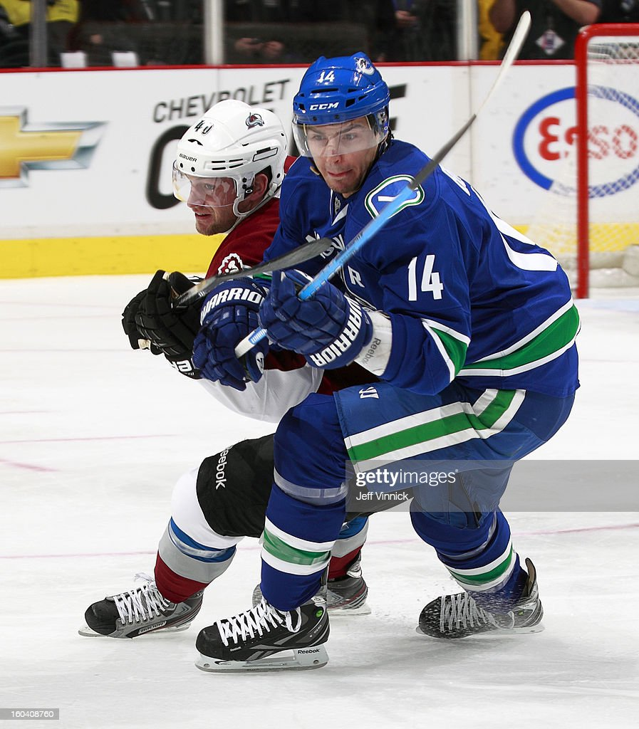 Mark Olver #40 of the Colorado Avalanche and <a gi-track='captionPersonalityLinkClicked' href=/galleries/search?phrase=Alexandre+Burrows&family=editorial&specificpeople=592489 ng-click='$event.stopPropagation()'>Alexandre Burrows</a> #14 of the Vancouver Canucks at close quarters during their NHL game at Rogers Arena January 30, 2013 in Vancouver, British Columbia, Canada. Vancouver won 3-0.