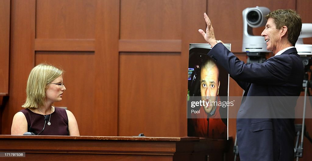 Mark O'Mara, George Zimmerman's attorney, displays a photo of Zimmerman taken the night of the shooting of Trayvon Martin, to Zimmerman's physician, Lindzee Folgate, during her testimony on the 15th day of Zimmerman's trial in Seminole circuit court June 28, 2013 in Sanford, Florida. Zimmerman is charged with second-degree murder for the February 2012 shooting death of 17-year-old Trayvon Martin.