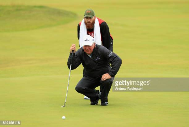 Mark O'Meara of the United States and his caddie line up a putt on the 3rd green during the first round of the 146th Open Championship at Royal...
