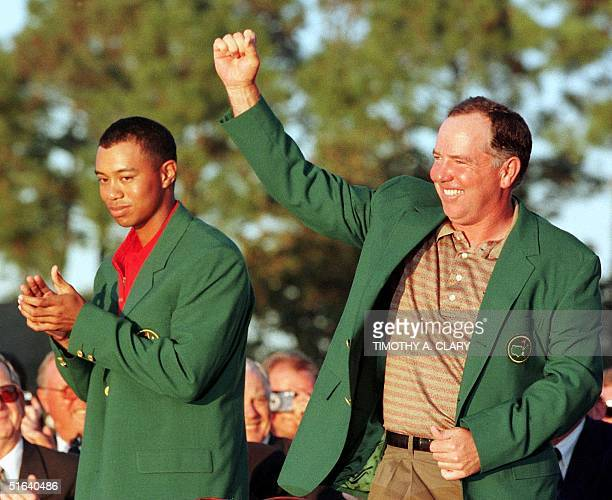 Mark O'Meara of the US pumps his fist in the air after getting the Green Jacket from Tiger Woods the defending Masters champion 12 April at Augusta...