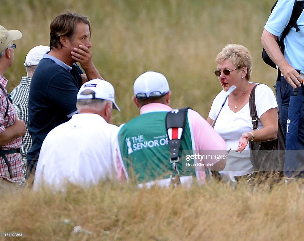 Mark O'Meara of the USA goes to the aid of a golf fan who was hit by his errant shot during the first round of The Senior Open Championship at Royal Birkdale on July 25, 2013 in Southport, England.