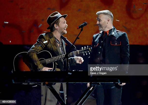 Mark Owen and Gary Barlow of Take That perform on stage at the BRIT Awards 2015 at The O2 Arena on February 25 2015 in London England