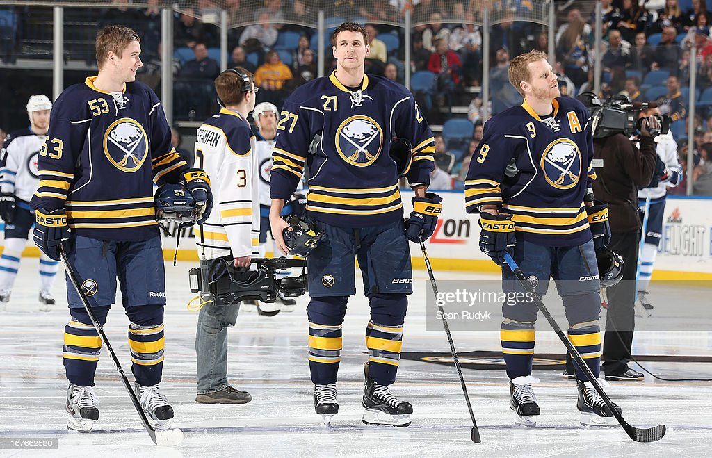 Mark Pysyk #53, Adam Pardy #27 and Steve Ott #9 of the Buffalo Sabres stand in respect of the playing of the Canadian and American national anthems before their game against the Winnipeg Jets at First Niagara Center on April 22, 2013 in Buffalo, New York.
