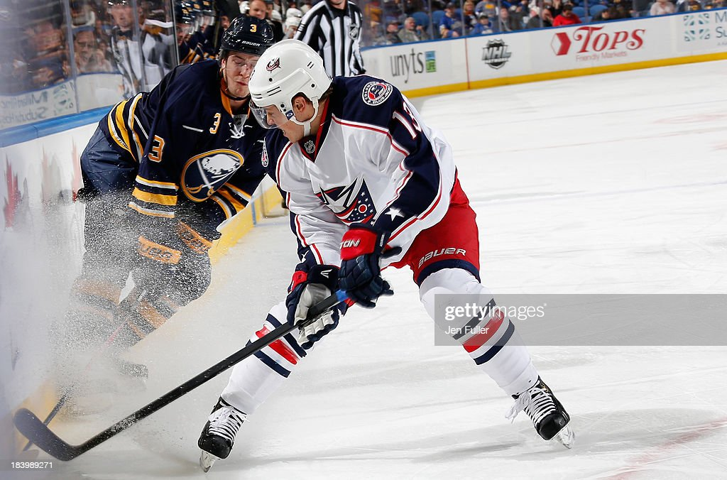 Mark Pysyk of the Buffalo Sabres and Cam Atkinson of the Columbus Blue Jackets battle for the puck along the boards at First Niagara Center on...