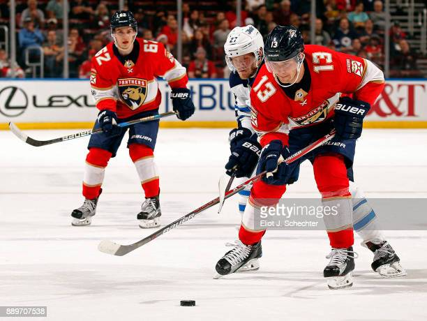 Mark Pysyk of the Florida Panthers skates for the puck against Nikolaj Ehlers of the Winnipeg Jets at the BBT Center on December 7 2017 in Sunrise...