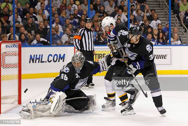 Mark Recchi of Boston Bruins is slowed down in front of the net by Mike Lundin and Dwayne Roloson of the Tampa Bay Lightning in Game Three of the...