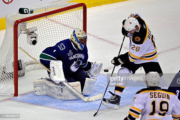 Mark Recchi of the Boston Bruins scores a goal off of a deflection from Zdeno Chara in the second period against Roberto Luongo of the Vancouver...