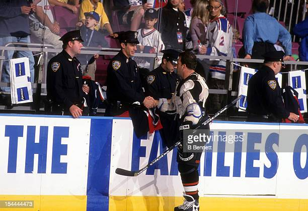 Mark Recchi of the Philadelphia Flyers shakes hands with an New York Police officer during a tribute to the victims of the September 11 attacks on...