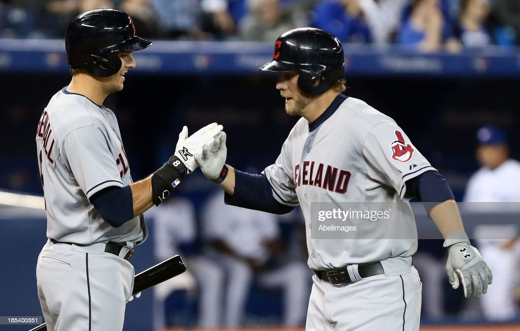 Mark Reynolds #12 and Lonnie Chisenhall #8 of the Cleveland Indians celebrate Reynolds's game-winning homer against the Toronto Blue Jays in the 11th inning during MLB action at the Rogers Centre April 3, 2013 in Toronto, Ontario, Canada.