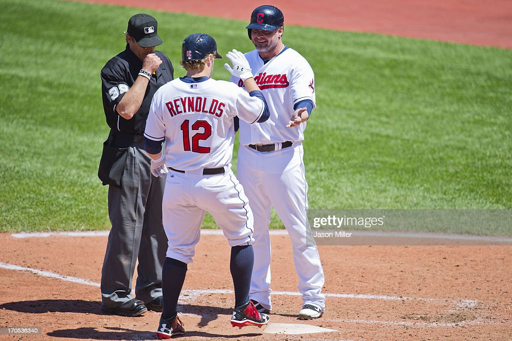 <a gi-track='captionPersonalityLinkClicked' href=/galleries/search?phrase=Mark+Reynolds+-+Baseball+Player&family=editorial&specificpeople=2343799 ng-click='$event.stopPropagation()'>Mark Reynolds</a> #12 celebrates a homer with <a gi-track='captionPersonalityLinkClicked' href=/galleries/search?phrase=Jason+Giambi&family=editorial&specificpeople=194953 ng-click='$event.stopPropagation()'>Jason Giambi</a> #25 of the Cleveland Indians as umpire Paul Nauert #39 watches the tag during the fifth inning against the Cleveland Indians at Progressive Field on May 9, 2013 in Cleveland, Ohio.
