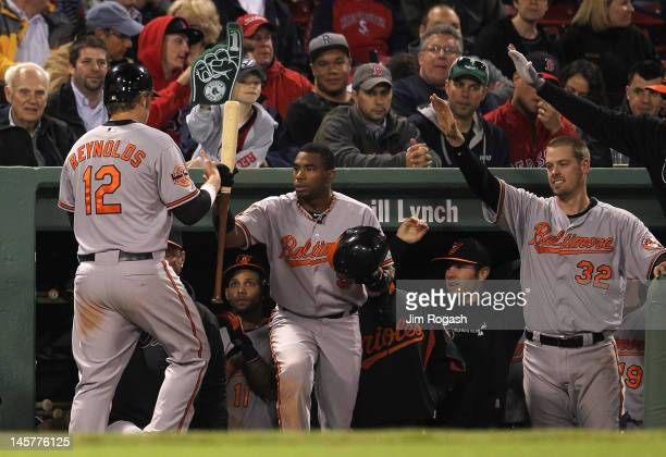 Mark Reynolds of the Baltimore Orioles celebrates with teammates after scored the winning on a hit by Ronny Paulino of the Baltimore Orioles in the...