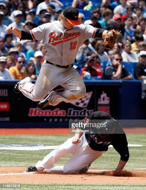 Mark Reynolds of the Baltimore Orioles misses the tag on Aaron Hill of the Toronto Blue Jays during MLB action at The Rogers Centre June 16 2011 in...