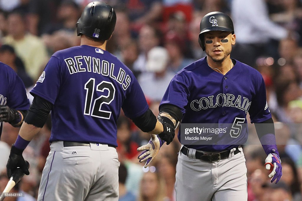 Mark Reynolds #12 of the Colorado Rockies congratulates Carlos Gonzalez #5 after he hit a two run homer against the Boston Red Sox during the fourth inning at Fenway Park on May 26, 2016 in Boston, Massachusetts.