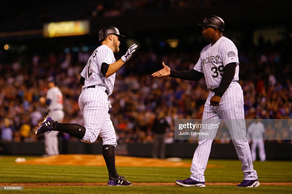 Mark Reynolds #12 of the Colorado Rockies is congratulated by third base coach Stu Cole of the Colorado Rockies on his three-run home run during the fourth inning against the Atlanta Braves at Coors Field on August 16, 2017 in Denver, Colorado.