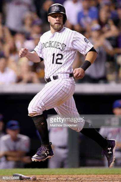 Mark Reynolds of the Colorado Rockies scores on a Carlos Gonzalez single in the eighth inning against the New York Mets at Coors Field on August 1...