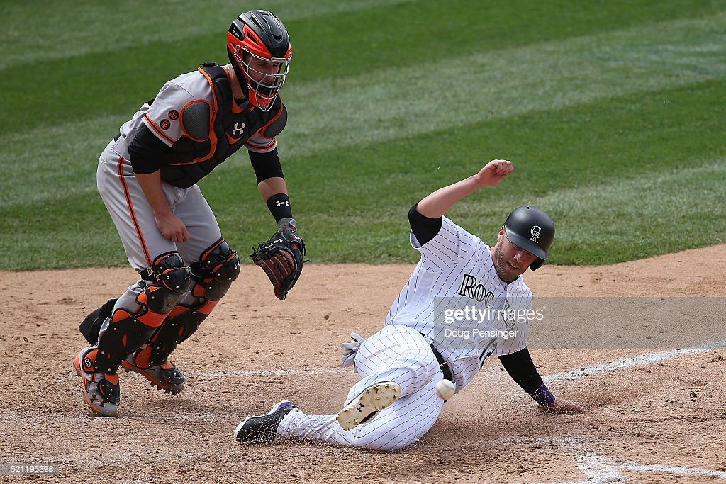 Mark Reynolds #12 of the Colorado Rockies slides home to score as he is hit by the ball on the throw from Angel Pagan #16 of the San Francisco Giants on a single by Ben Paulsen #10 of the Colorado Rockies as catcher Buster Posey #28 of the San Francisco Giants can't reach the ball as Rockies take a 9-1 lead in the fifth inning at Coors Field on April 14, 2016 in Denver, Colorado.