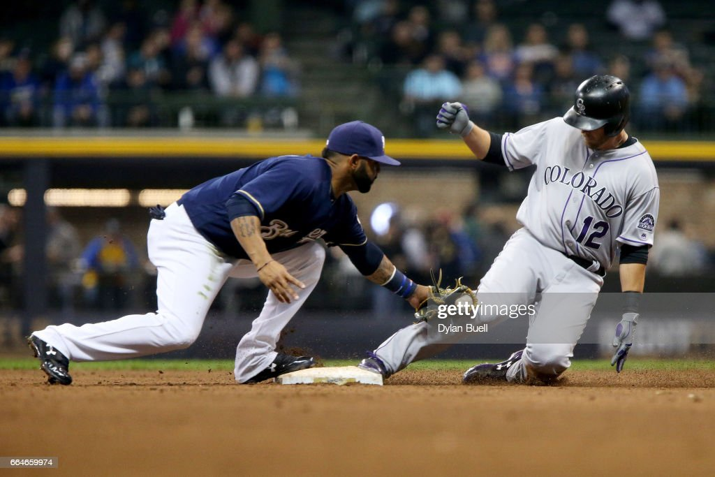 Mark Reynolds #12 of the Colorado Rockies slides into second base for a double past Jonathan Villar #5 of the Milwaukee Brewers in the fifth inning at Miller Park on April 4, 2017 in Milwaukee, Wisconsin.
