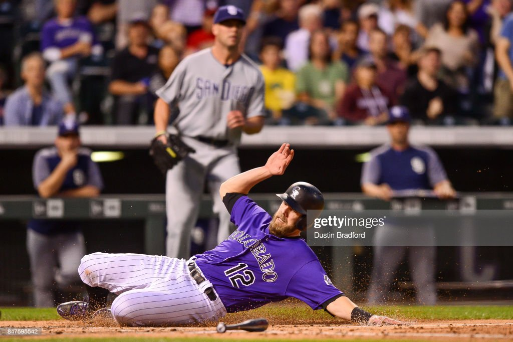 Mark Reynolds #12 of the Colorado Rockies slides past home plate as he scores a run against the San Diego Padres int he second inning of a game at Coors Field on September 15, 2017 in Denver, Colorado.