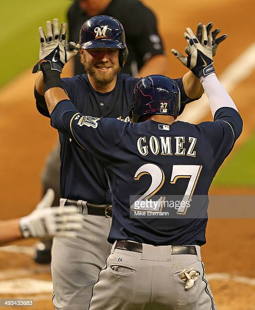 Mark Reynolds of the Milwaukee Brewers is congratulated by Carlos Gomez after hitting a two run home run during a game against the Miami Marlins at...