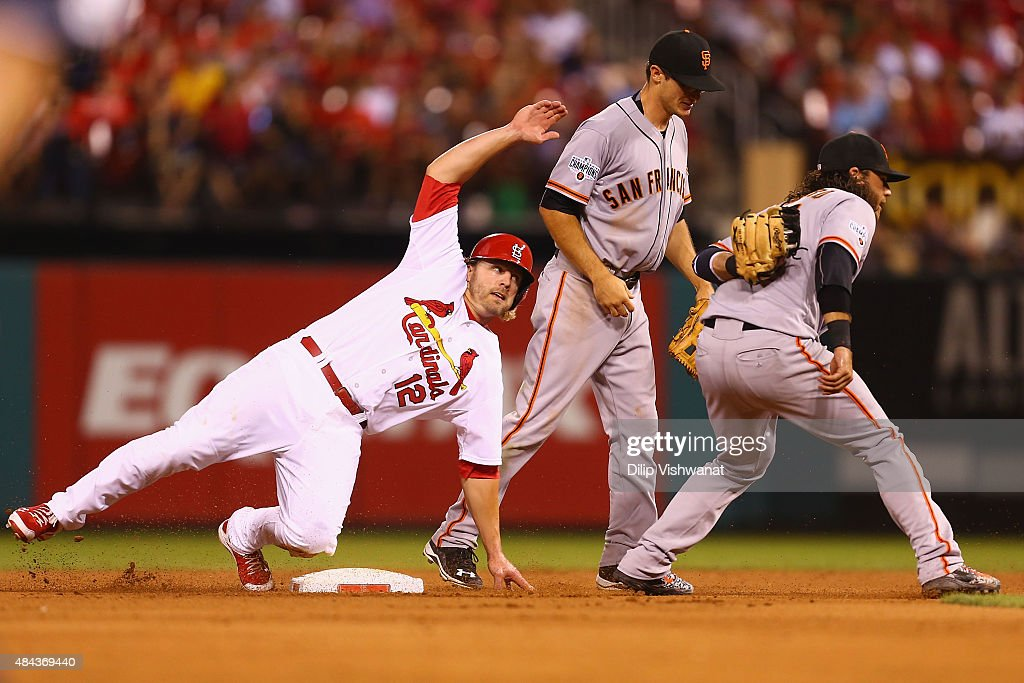 Mark Reynolds #12 of the St. Louis Cardinals is caught stealing second base by Brandon Crawford #35 of the San Francisco Giants as Kelby Tomlinson #37 of the Giants looks on in the eighth inning at Busch Stadium on August 17, 2015 in St. Louis, Missouri.