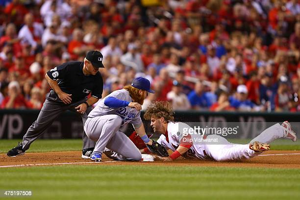 Mark Reynolds of the St Louis Cardinals is caught stealing third base by Justin Turner of the Los Angeles Dodgers as umpire Mike Muchlinski looks on...