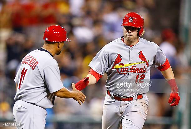 Mark Reynolds of the St Louis Cardinals is congratulated by Jose Oquendo after hitting a solo home run in the 10th inning against the Pittsburgh...