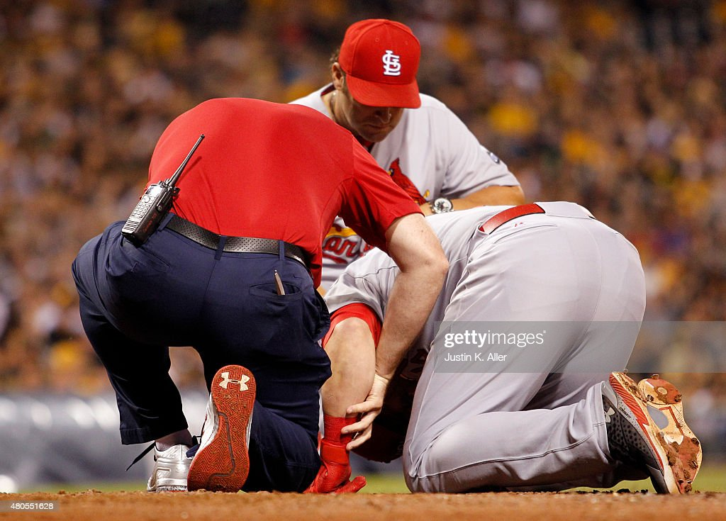 Mark Reynolds #12 of the St. Louis Cardinals is tended to by medical staff after being hit by a pitch in the tenth inning during the game against the Pittsburgh Pirates at PNC Park on July 12, 2015 in Pittsburgh, Pennsylvania.