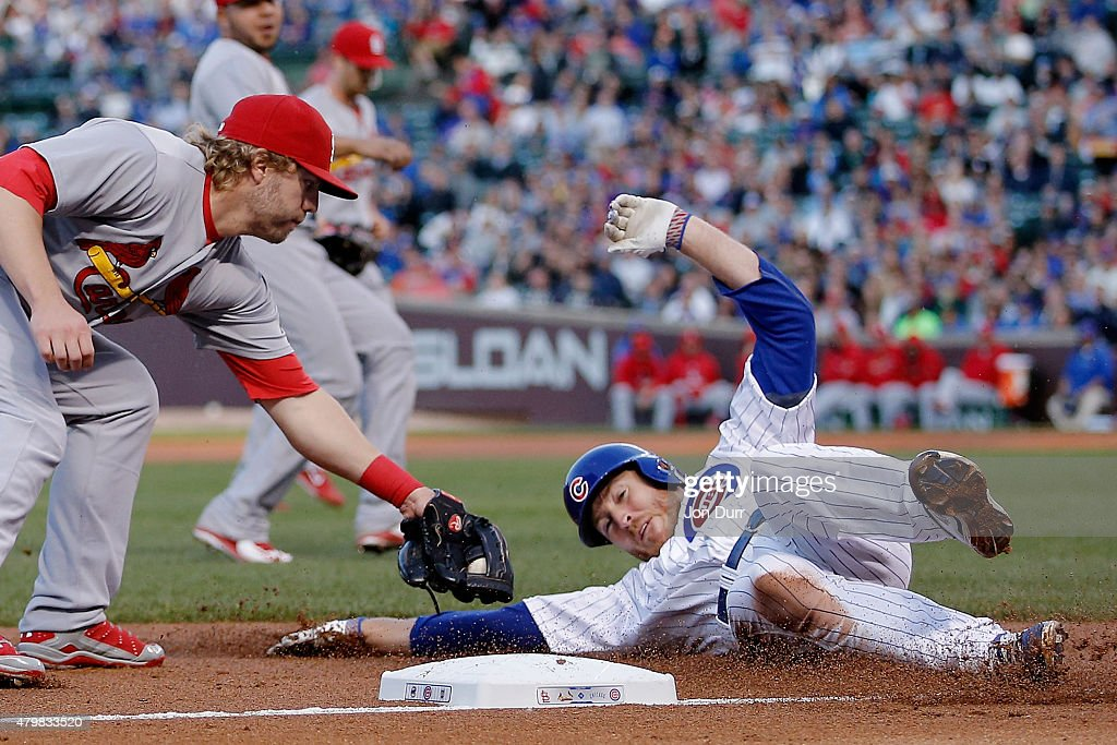 Mark Reynolds #12 of the St. Louis Cardinals tags out Chris Denorfia #15 of the Chicago Cubs at third base during the third inning during game two of a double header at Wrigley Field on July 7, 2015 in Chicago, Illinois.