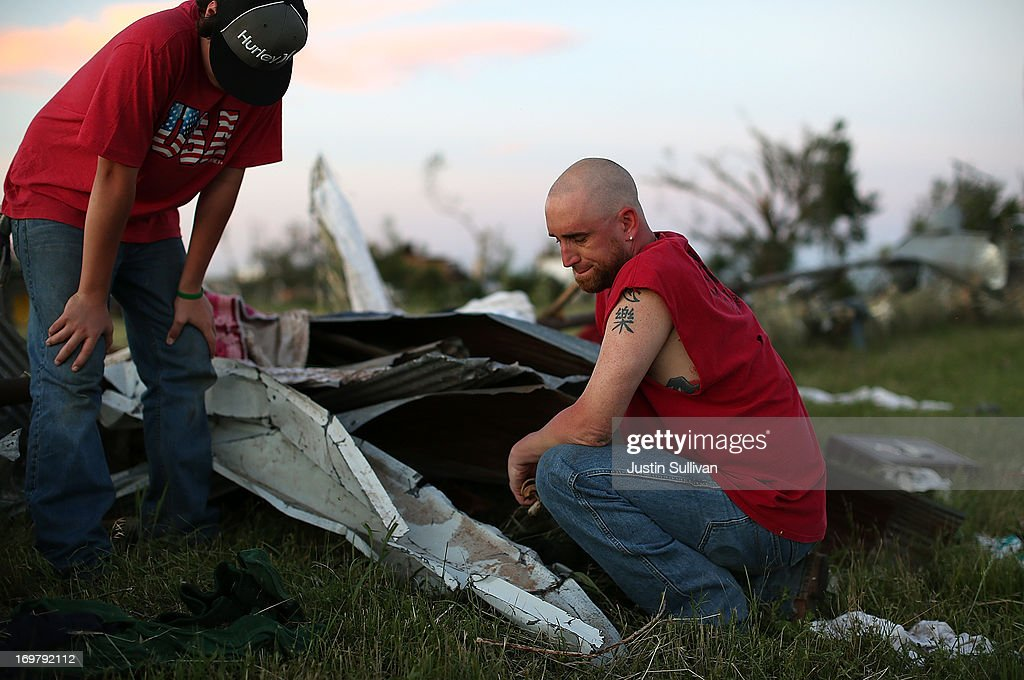 Mark Reynolds (R) pauses while looking through debris to find personal items after a series of tornadoes that ripped through the area a day earlier on June 1, 2013 in El Reno, Oklahoma. A series of tornadoes ripped through the area on Friday evening killing at least nine people, injuring many others and destroying homes and buildings.
