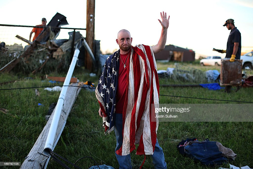 Mark Reynolds waves to a passing car as he looks through debris to find personal items after a series of tornadoes that ripped through the area a day earlier on June 1, 2013 in El Reno, Oklahoma. A series of tornadoes ripped through the area on Friday evening killing at least nine people, injuring many others and destroying homes and buildings.