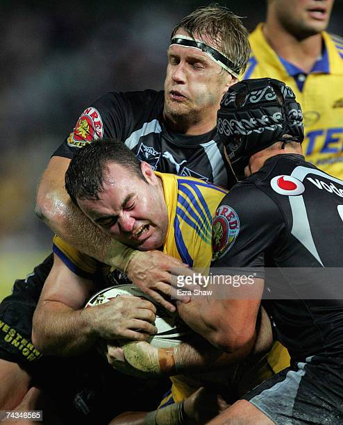 Mark Riddell of the Eels is tackled by Micheal Luck and Tony Martin of the Warriors during the round 11 NRL match between the Parramatta Eels and the...