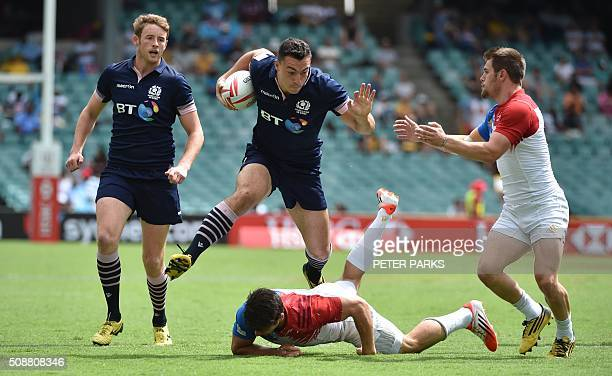 Mark Robertson of Scotland watches as teammate Jamie Farndale avoids a tackle by Martin Laveau of France as his teammate Stephen Parez looks on...