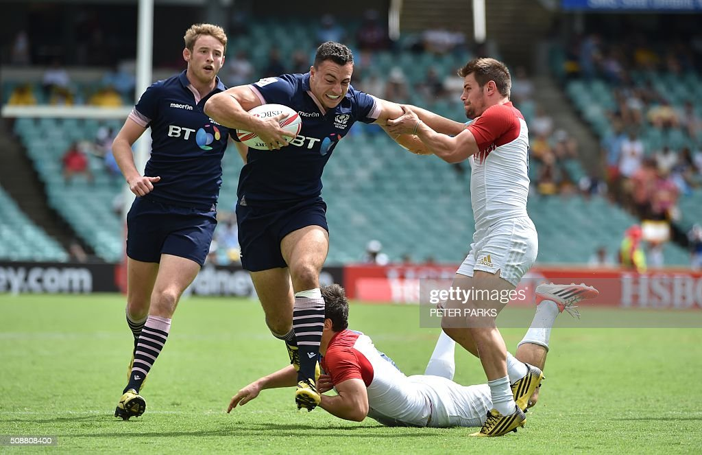 Mark Robertson of Scotland (L) watches as teammate Jamie Farndale (C) avoids a tackle by Martin Laveau of France (bottom) as his teammate Stephen Parez (R) tackles him during their Bowl quarter-final game at the Sydney Sevens rugby union tournament in Sydney on February 7, 2016. AFP PHOTO / Peter PARKS PARKS