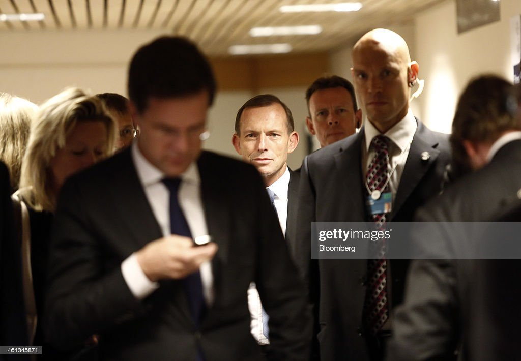 Mark Rutte Dutch prime minister left looks as his mobile handset as Tony Abbott Australia's prime minister center walks between venues during a break...