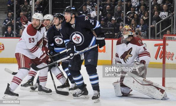 Mark Scheifele and Blake Wheeler of the Winnipeg Jets stand between Derek Morris Rostislav Klesla and goaltender Mike Smith of the Phoenix Coyotes as...
