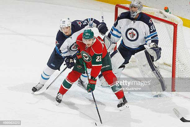 Mark Scheifele and goalie Connor Hellebuyck defend their goal against Nino Niederreiter of the Minnesota Wild during the game on November 27 2015 at...