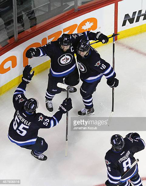 Mark Scheifele and Jacob Trouba of the Winnipeg Jets join teammates Andrew Ladd and Bryan Little to celebrate an overtime goal against the Colorado...