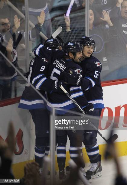 Mark Scheifele and Mark Stuart of the Winnipeg Jets congratulate teammate Evander Kane for his goal against the Los Angeles Kings in first period...