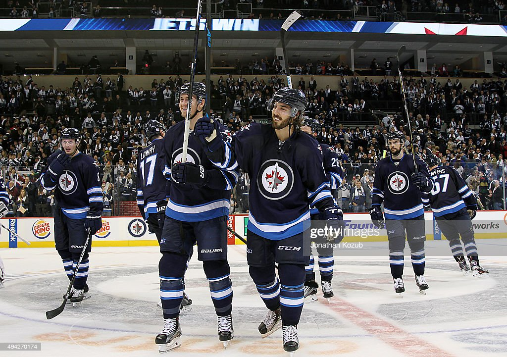 Mark Scheifele #55 and Mathieu Perreault #85 of the Winnipeg Jets are all smiles as they salute the fans following a 5-4 victory over the Minnesota Wild at the MTS Centre on October 25, 2015 in Winnipeg, Manitoba, Canada.