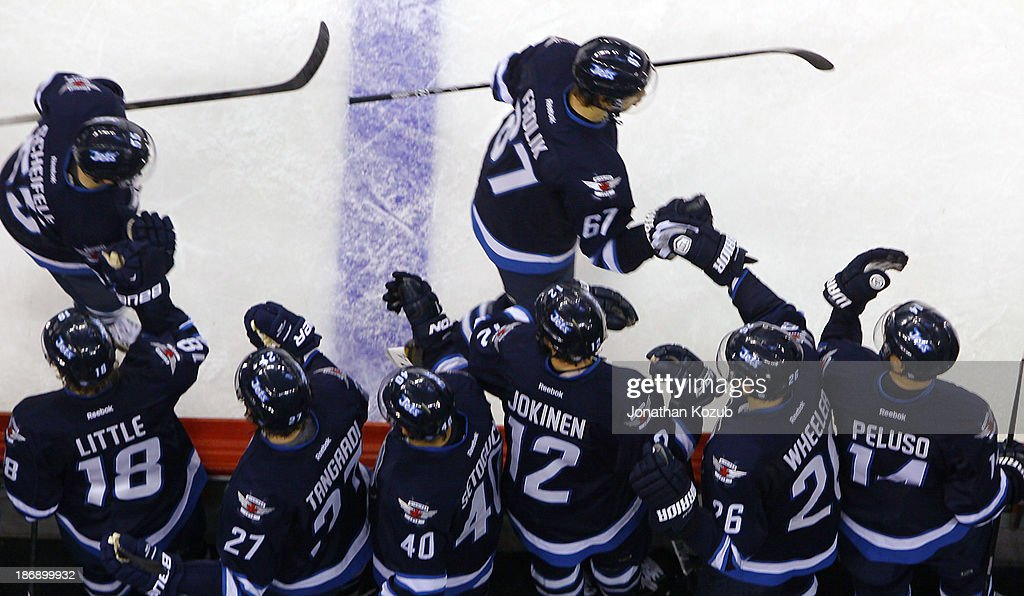 Mark Scheifele #55 and Michael Frolik #67 of the Winnipeg Jets celebrate with teammates at the bench following a second period goal against the Detroit Red Wings at the MTS Centre on November 4, 2013 in Winnipeg, Manitoba, Canada.
