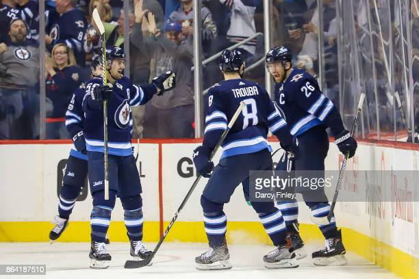 Mark Scheifele Jacob Trouba and Blake Wheeler of the Winnipeg Jets celebrate a third period goal against the Minnesota Wild at the Bell MTS Place on...