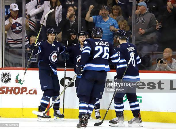 Mark Scheifele Kyle Connor Blake Wheeler and Jacob Trouba of the Winnipeg Jets celebrate a second period goal against the New Jersey Devils at the...