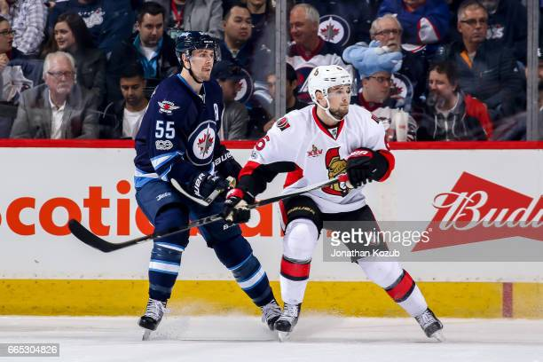 Mark Scheifele of the Winnipeg Jets and Chris Wideman of the Ottawa Senators keep an eye on the play during first period action at the MTS Centre on...