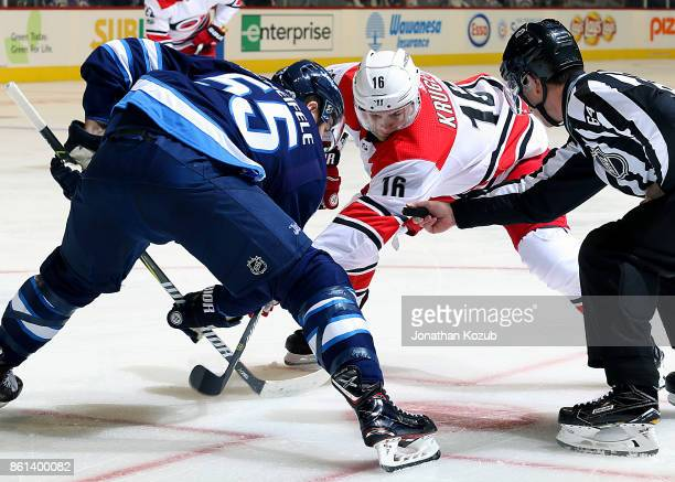 Mark Scheifele of the Winnipeg Jets and Marcus Kruger of the Carolina Hurricanes eye the puck as they await a first period faceoff at the Bell MTS...