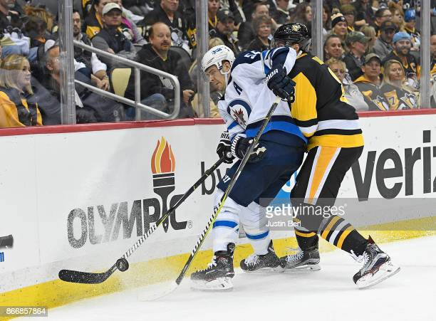 Mark Scheifele of the Winnipeg Jets battles along the boards for the puck with Brian Dumoulin of the Pittsburgh Penguins in the third period during...