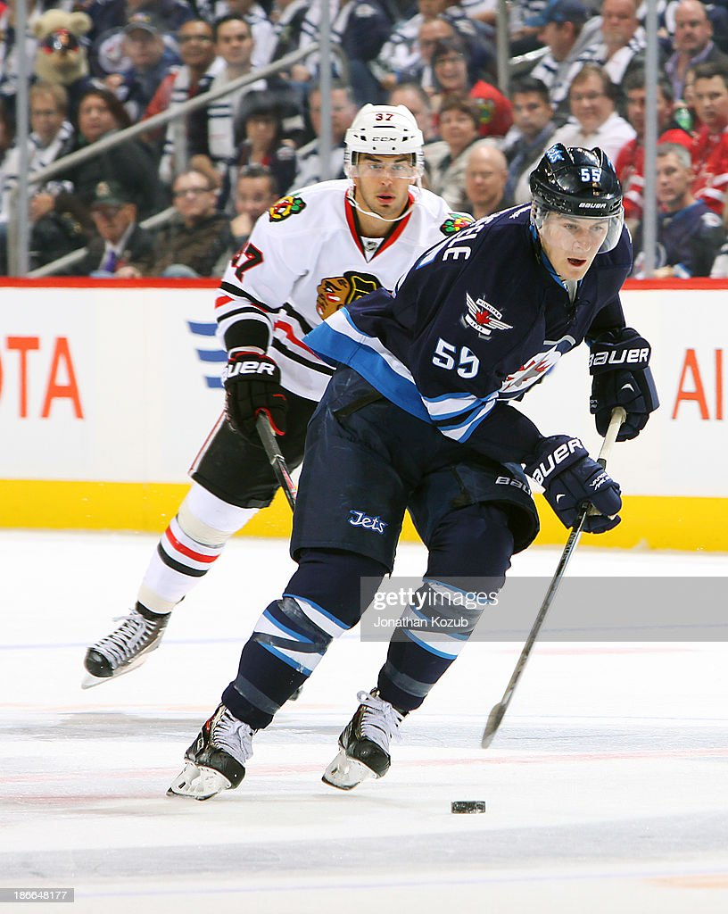 <a gi-track='captionPersonalityLinkClicked' href=/galleries/search?phrase=Mark+Scheifele&family=editorial&specificpeople=7342540 ng-click='$event.stopPropagation()'>Mark Scheifele</a> #55 of the Winnipeg Jets carries the puck up the ice as <a gi-track='captionPersonalityLinkClicked' href=/galleries/search?phrase=Brandon+Pirri&family=editorial&specificpeople=5894589 ng-click='$event.stopPropagation()'>Brandon Pirri</a> #37 of the Chicago Blackhawks follows during third period action at the MTS Centre on November 2, 2013 in Winnipeg, Manitoba, Canada.