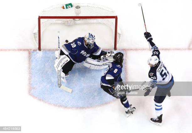 Mark Scheifele of the Winnipeg Jets celebrates his gamewinning goal against goalie Anders Lindback and Mark Barberio of the Tampa Bay Lightning...