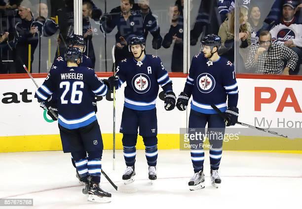 Mark Scheifele of the Winnipeg Jets celebrates his third period goal against the Toronto Maple Leafs with teammates Blake Wheeler Patrik Laine and...