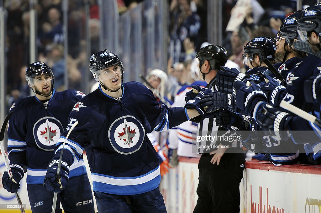 <a gi-track='captionPersonalityLinkClicked' href=/galleries/search?phrase=Mark+Scheifele&family=editorial&specificpeople=7342540 ng-click='$event.stopPropagation()'>Mark Scheifele</a> #55 of the Winnipeg Jets celebrates with teammates at the bench after scoring a third period goal against the Edmonton Oilers at the MTS Centre on January 18, 2014 in Winnipeg, Manitoba, Canada.