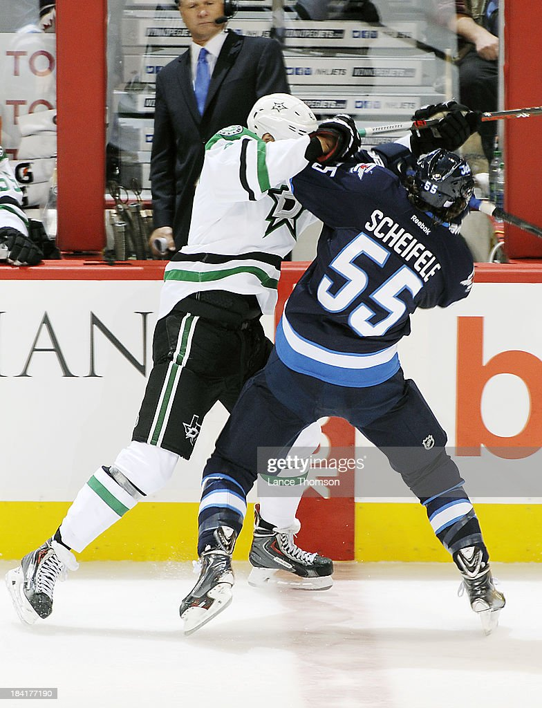 Mark Scheifele #55 of the Winnipeg Jets checks Valeri Nichushkin #43 of the Dallas Stars into the boards during second period action at the MTS Centre on October 11, 2013 in Winnipeg, Manitoba, Canada.